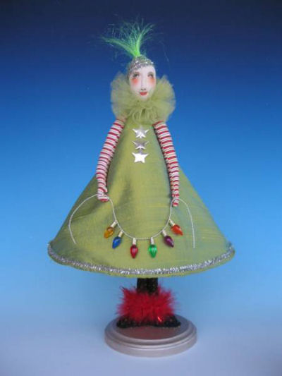 "The costume of this 15"" delight mimics a Christmas Tree using a wire to shape the skirt, miniature lights and stars for trim."