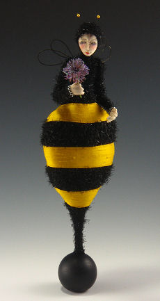 "Bee-utiful 14"" figure balancing on a wooden ball."