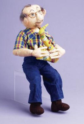 "Dedicated to her late husband Gary, this classic 18"" male doll is holding a stuffed saxophone, one of Gary's great loves."