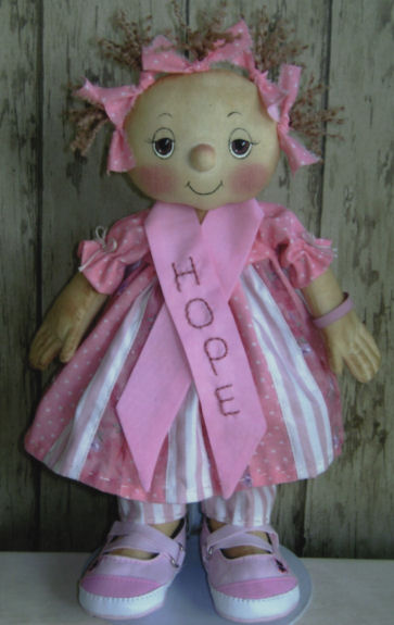 "You'll be stitching in the fingers of this sweet 12"" raggedy standing in real baby shoes. The designer's profits from this pattern are being donated to the Susan G. Komen Foundation for Breast Cancer."