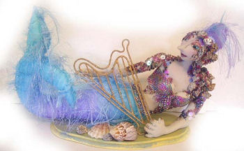 "With a tail made of eyelash fabric, this gorgeous 13"" reclining mermaid is"