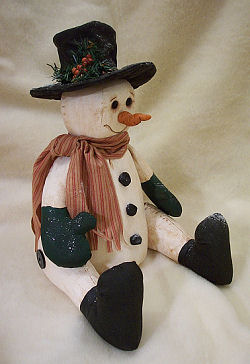 "This 13"" seated, primitive snowman is made of painted muslin with a clay nose."