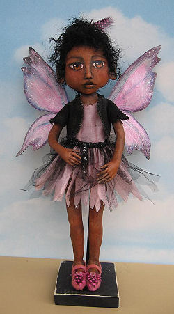 "16"" painted fairy with beautiful tyvek wings and a fringed tulle and fabric skirt."