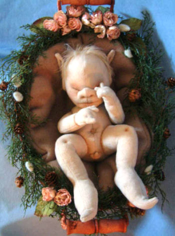 "Weighted throughout his body to feel like a real baby this 9"" anatomically correct newborn elf is snuggled in an easy-to-make flowered nest."